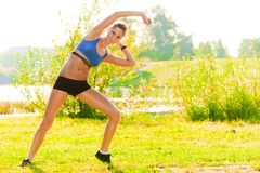 Trim  young woman performs stretching exercises in the park Stock Images