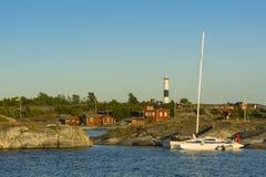 Trimaran moored to cliff Huvudskär Stockholm achipelago. Trimaran sailingboat in evening light moored to a cliff with Huvudskär lighthouse and the old stock photo