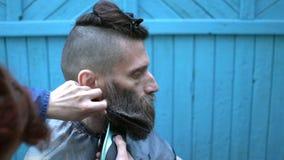 Triming Bart des Frauenfriseurs des merkwürdigen Hippie-Mannes von mittlerem Alter im experimentellen Friseursalon im Freien Mann stock footage