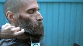 Triming Bart des jungen Schönheitsfriseurs des merkwürdigen Hippie-Mannes von mittlerem Alter im experimentellen Friseursalon im  stock footage
