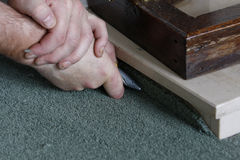 Triming the carpet Stock Images