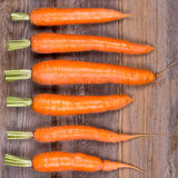 Trimmed carrots in a row. A row of trimmed fresh carrots on vintage style wood background Royalty Free Stock Photos