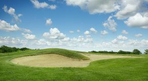 Trimmed field and sand bunkers on golf course. Trimmed field and sand bunkers for game on golf course, nobody. Green meadow in golfing club, playground in sunny royalty free stock images