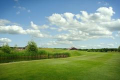 Trimmed field and sand bunkers on golf course. Trimmed field and sand bunkers for game on golf course, nobody. Green meadow in golfing club, playground in sunny royalty free stock photography