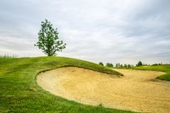 Trimmed field and sand bunkers on golf course. Trimmed field and sand bunkers for game on golf course, nobody. Green meadow in golfing club, playground in sunny stock photo