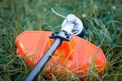 Trimmer στενός επάνω κόβει τη χλόη με το χορτοκόπτη στοκ φωτογραφίες με δικαίωμα ελεύθερης χρήσης