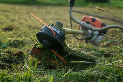 Trimmer after work lies on the grass Royalty Free Stock Photography
