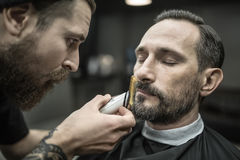 Trimming beard in barbershop Royalty Free Stock Photo