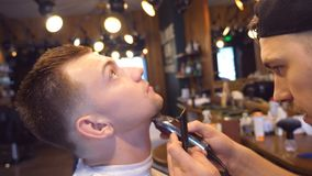 Trimming beard of male client with clipper at barber shop. Hairstyling process. Close up Slow motion.  stock footage