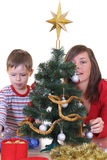 Trimming the christmas tree. Family decorating Christmas tree isolated on white Royalty Free Stock Image