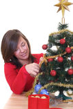 Trimming the christmas tree. Young woman decorating Christmas tree isolated on white Royalty Free Stock Photography