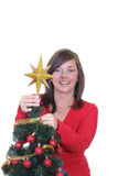 Trimming the christmas tree. Young woman decorating Christmas tree isolated on white Stock Photography
