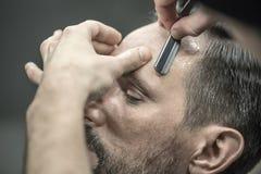 Trimming hair in barbershop. Bearded men in the barbershop. Barber is trimming his hair with a straight razor. Closeup. Horizontal Stock Images