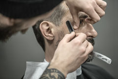 Trimming hair in barbershop Stock Photography