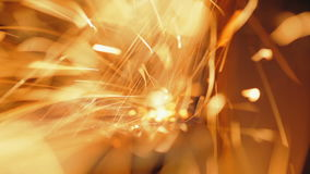 Trimming of metal products. Lots of sparks. Sharpening of metal products. In the picture a lot of sparks flying into the camera lens. Lots of sparks stock footage