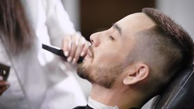 Trimming mustache in barber shop. Young hipster visiting barber shop. stock video footage