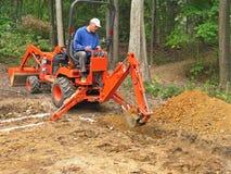 Trincea di scavatura dell'uomo con l'escavatore a cucchiaia rovescia fotografia stock