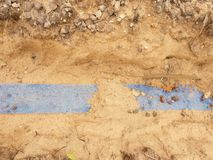 Trincheira com a fita plástica azul da proteção Marcado dos cabos sob a argila durante a construção do Internet fotografia de stock royalty free