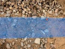 Trincheira com a fita plástica azul da proteção Marcado dos cabos sob a argila durante a construção do Internet fotos de stock