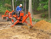 Trincheira de escavação do homem com backhoe Fotografia de Stock