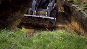 Trincheira de escava??o do mini carregador em trabalhos da terra com grama verde no primeiro plano filme