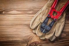 Trinciatrice per bulloni dei guanti protettivi sul conce della costruzione del bordo di legno Fotografie Stock Libere da Diritti