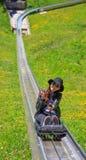 Trineo asiático del trineo largo del verano del montar a caballo de la mujer abajo de una colina a través del prado hermoso de la Imagenes de archivo