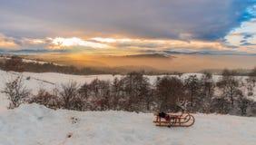 Trineo colorido del cielo y de la puesta del sol de la monta?a del invierno en el primero plano foto de archivo
