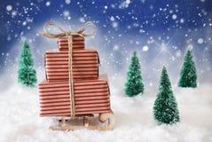 Trineo de la Navidad en nieve con el fondo, los copos de nieve y las estrellas azules Foto de archivo libre de regalías