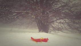 Trineo rojo abandonado en la nieve Fotos de archivo libres de regalías