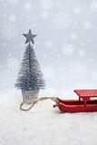 Trineo rojo y árbol ornamental Fotografía de archivo