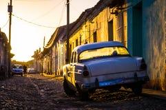 Trinidad, Cuba: Calle con el oldtimer en la puesta del sol Fotos de archivo libres de regalías