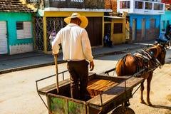 Trinidad, Cuba - 2019.Cuban man offloading bricks from a horse drawn carriage stock photo