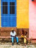 Trinidad, Cuba Em junho de 2016 Assento de dois homens negros exterior e conversa na rua de Trinidad imagens de stock royalty free