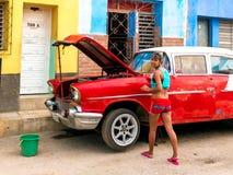 Trinidad, Cuba Em junho de 2016: Carro da fixação da mulher Jovem mulher local que repara um gato velho do vintage imagens de stock