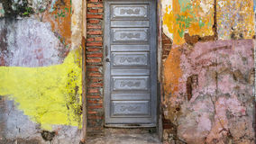 Trinidad, Cuba Facade 1. Colorful building with silver metal door and brick from the streets of Trinidad, Cuba. Featuring layers of weathered stucco and chipping Stock Photo