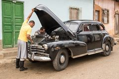 Classic 1950`s Ford. Trinidad, Cuba, Nov 27, 2017 - Black 1950`s Class America Ford with hood up, being worked on. Car also has dent patches visible royalty free stock photo