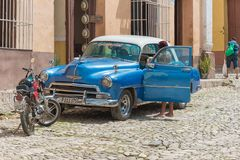 Trinidad,Cuba: Old Chevrolet car in cobblestone street. Everyday candid scenes of the Spanish colonial village which is a Unesco World Heritage Site and major Royalty Free Stock Image