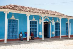 Trinidad, Cuba - people sitting in front of a blue house stock image