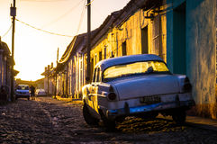 Trinidad, Cuba: Street with oldtimer at sunset. Sunset light shining on street with a white oldtimer in Trinidad, Cuba Stock Photos