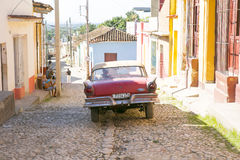 Trinidad, Cuba Street Scene. Vintage Ford Fairlane car driving down cobblestone street of Trinidad, Cuba. Taken December, 2015 Royalty Free Stock Photos
