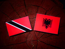 Trinidad and Tobago flag with Albanian flag on a tree stump isol Royalty Free Stock Photography