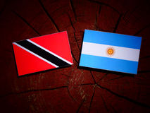 Trinidad and Tobago flag with Argentinian flag on a tree stump i. Trinidad and Tobago flag with Argentinian flag on a tree stump Stock Photos