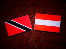 Trinidad and Tobago flag with Austrian flag on a tree stump isol Royalty Free Stock Image