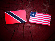 Trinidad and Tobago flag with Liberian flag on a tree stump isol. Ated Stock Images