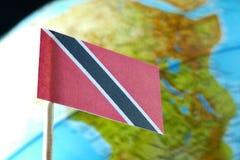 Trinidad and Tobago señalan por medio de una bandera con un mapa del globo como fondo Imágenes de archivo libres de regalías