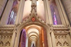Trinidad Windows con colores brillantes dentro de la catedral, vista a través de un arco con las tallas Foto de archivo libre de regalías