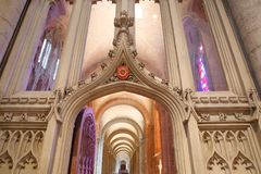 Trinità Windows con i colori luminosi dentro la cattedrale, osservata attraverso un arco con le sculture Fotografia Stock Libera da Diritti