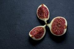 Trinité des figues fraîches coupées sur le schiste noir Photographie stock