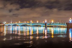 The Trinity Bridge night with backlight illumination lights with reflection in the river Neva, Saint-Petersburg. The Trinity Bridge night with backlight Royalty Free Stock Photos